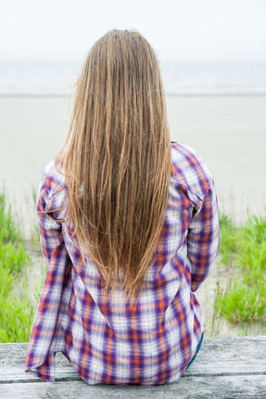 Back view of young woman with long blond hair sitting on misty beach facing ocean wearing plaid shirt