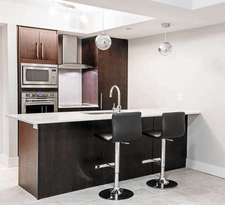 Modern luxury kitchen interior with dark wood cabinets, island counter, bar stools and stainless steel appliances Banque d'images