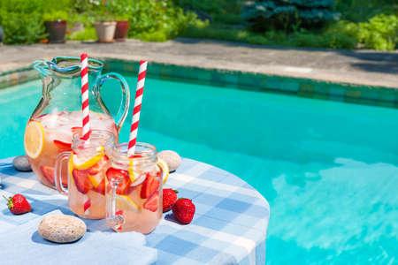 Ijskoude zelfgemaakte Strawberry limonade in kruik en glazen met papier rietjes op buiten de zomer aan het zwembad tafel plus kopiëren ruimte