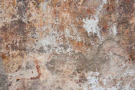 Abstract background of old painted plastered wall with peeling paint texture in brown, grey, and orange colors Stockfoto