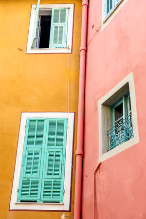 Windows with shutters on brightly coloured houses in medieval town Villefranche-sur-Mer on French Riviera, France.