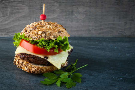 Gourmet hamburger with swiss cheese, fresh vegetables on multigrain bun against dark background and copy space