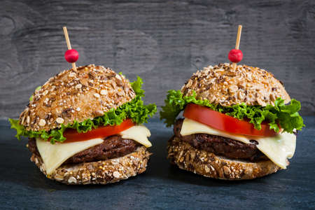 Two gourmet hamburgers with swiss cheese and fresh vegetables on multigrain buns over dark background