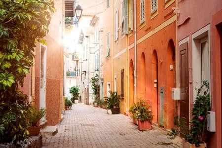 Stretta di sole vecchia strada con edifici colorati dipinti e piante in vaso verdi nella città medievale di Villefranche-sur-Mer sulla Costa Azzurra, Francia. Archivio Fotografico
