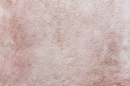 Old vintage plastered stucco wall brushed texture abstract background in faded pink color
