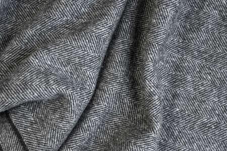 Draped herringbone tweed background with closeup on wool fabric texture