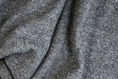 Draped herringbone tweed background with closeup on wool fabric texture
