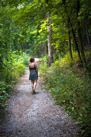 Contemplative young woman wearing summer dress standing on path in green dense forest