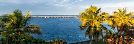 View of Overseas Highway framed by palm trees from historic Rail Bridge at Bahia Honda state park in Florida Keys, USA.