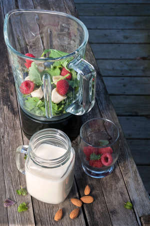Blender with healthy smoothie ingredients - almond milk, fresh fruit, baby kale - on rustic wood table. Archivio Fotografico