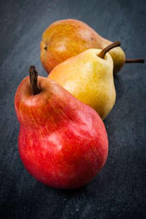 Three bright ripe bartlett pears on dark grey background Stock Photo