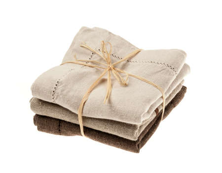 Linen cloth napkins in brown and beige natural colors folded and tied with string isolated on white background