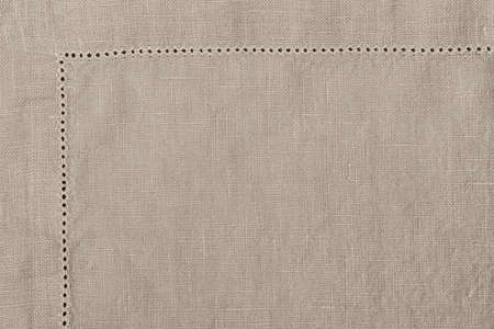 Edge of linen cloth napkin in natural color, macro closeup on fabric texture.