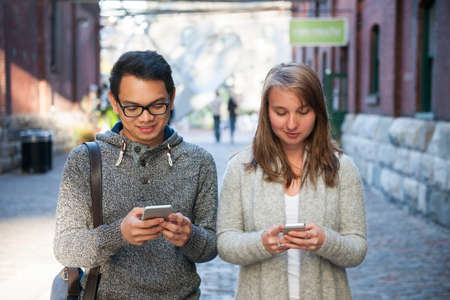 Two young people looking into smartphones while walking on city street Imagens - 52396772