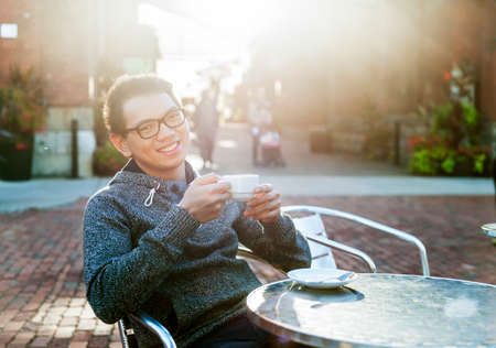 Young asian man sitting and smiling in outdoor cafe holding cup of coffee, intentional lens flare.