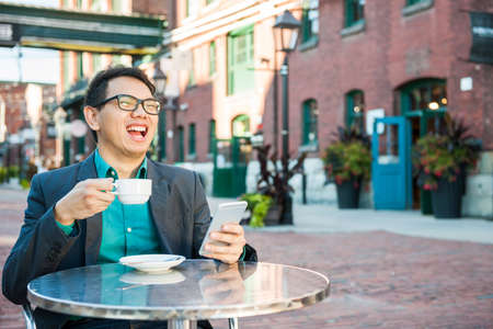 Laughing young asian man sitting in outdoor cafe with mobile phone holding cup of coffee enjoying success Stockfoto