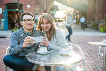 2 つの屋外カフェでテーブルに座ってスマート フォンを探している若者を笑う