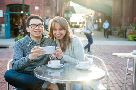 Two laughing young people looking into smartphone while sitting at a table in outdoor cafe Foto de archivo