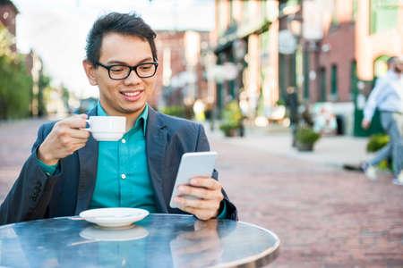 ビジネスカジュアルな服装に座って、携帯電話を使用しながら一杯のコーヒーを飲んでリラックスした屋外カフェで笑顔の若い男性