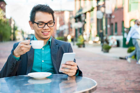 Young asian man in business casual attire sitting and smiling in relaxing outdoor cafe drinking cup of coffee while using mobile phone Imagens - 55759726