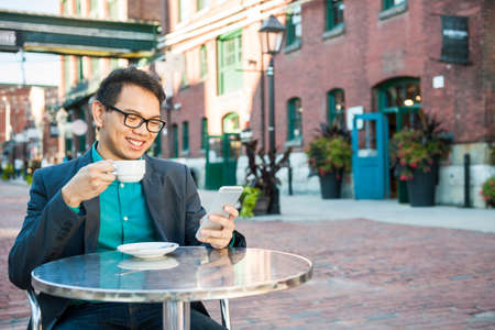 Young asian man in business casual attire sitting and smiling in relaxing outdoor cafe drinking cup of coffee while using mobile phone, with copy space.