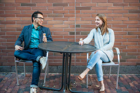 Two smiling young people with ice cream sitting at outdoor cafe table near brick wall having conversation Reklamní fotografie