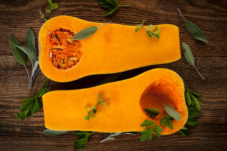 Fresh butternut squash cut in half with sage and parsley on brown wooden background, from above