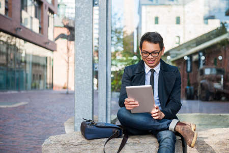 Young smiling asian business man looking at digital tablet sitting outside on city street