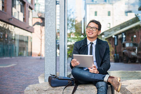 Young smiling asian business man holding a digital tablet sitting outside on city street looking away Stockfoto