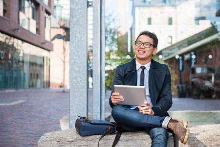Junge lächelnde asiatische Geschäftsmann, der eine digitale Tablette hält draußen auf Stadtstraße weg schauen sitzt