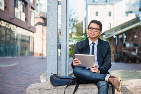 Young  asian business man holding a digital tablet sitting outside on city street looking thoughtful and concerned Stock Photo - 60657883