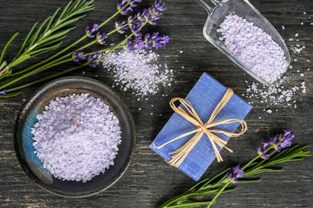 Bath salts and handmade soap herbal body care products with fresh lavender on rustic wooden background