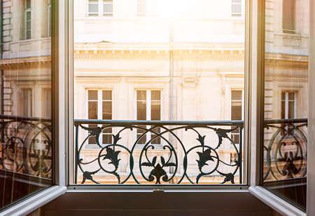 後半の午後の陽にフランスのトゥールーズで開いているウィンドウからヨーロッパの建物の眺め。