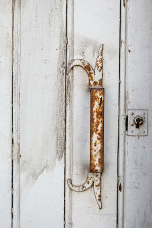 Rusty metal handle on antique painted white wooden door in Toulouse, France, closeup.