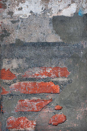 Abstract background of red bricks showing though layers of cement and plaster. Building fragment in Toulouse, France. Stok Fotoğraf