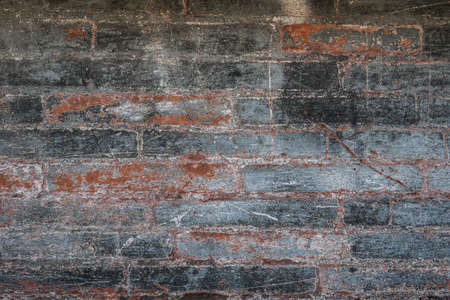 Antique brick wall with red bricks showing though layers of gray paint. Abstract background of building fragment in Toulouse, France. Imagens