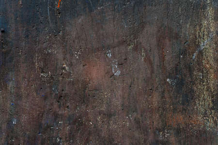Abstract background of old painted plastered brown wall with layers peeling paint and distressed plaster texture.