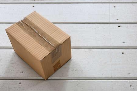 Cardboard delivery parcel box delivered to doorstep closeup