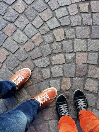Benen en voeten van twee mensen die tennisschoenen dragen die zich op keibestrating bevinden van hierboven met exemplaarruimte
