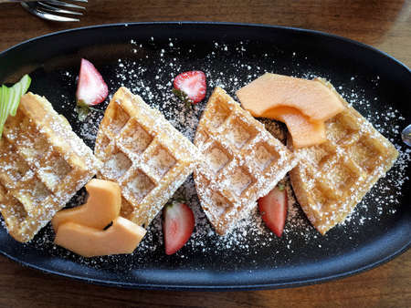 Belgium waffles with fruit and powdered sugar on breakfast plate, overhead view