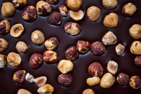 Artisanal dark chocolate bar with whole hazelnuts as background, closeup.