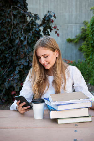 Smiling young woman student with books and binders distracted by phone while studying in a study area of university or college campus Standard-Bild