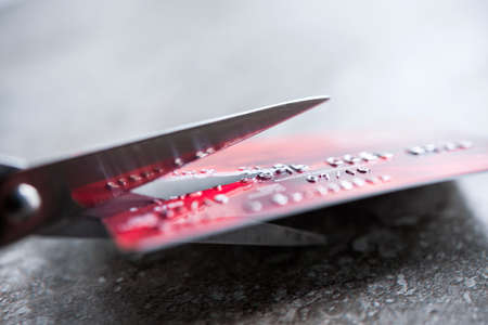Credit card being cut with scissors, close up with copy space Фото со стока