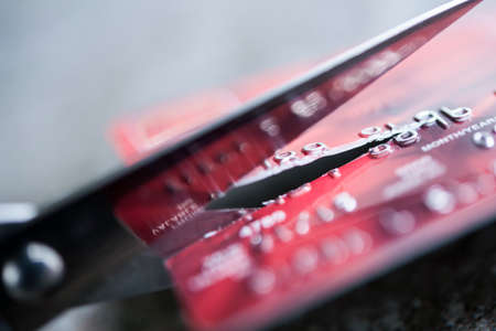 Credit card being cut with scissors, close up.