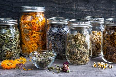 Diverse droge geneeskrachtige kruiden en kruidenthee in verscheidene glaskruiken op grijze houten achtergrond, sluiten omhoog