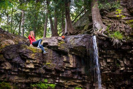 젊은 여자 등산객 여름 포리스트의 폭포 옆에 앉아. 힐튼 폭포 보존 지역, 온타리오, 캐나다입니다.