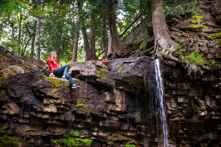 Young woman hiker sitting next to waterfall in summer forest. Hilton Falls conservation area, Ontario, Canada. Фото со стока