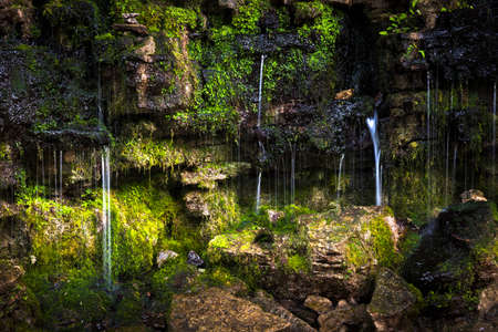 Small waterfall over moss covered rocks with sunshine. Hilton Falls conservation area, Ontario, Canada.