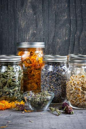 Verschillende gedroogde geneeskrachtige kruiden en kruidenthee in verschillende glazen potten op grijze houten achtergrond