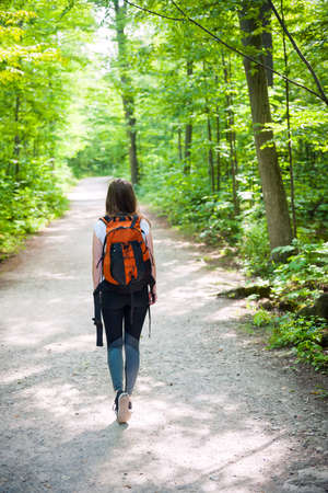 Young woman hiker with backpack walking on hiking trail in sunny summer forest. Hilton Falls conservation area, Ontario, Canada.